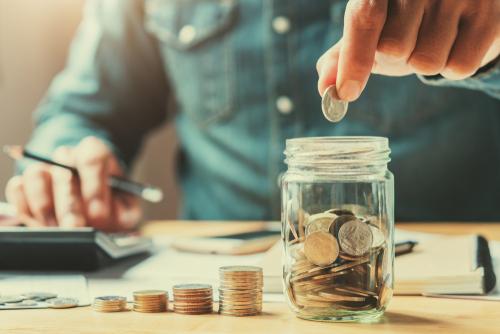man placing coins in jar